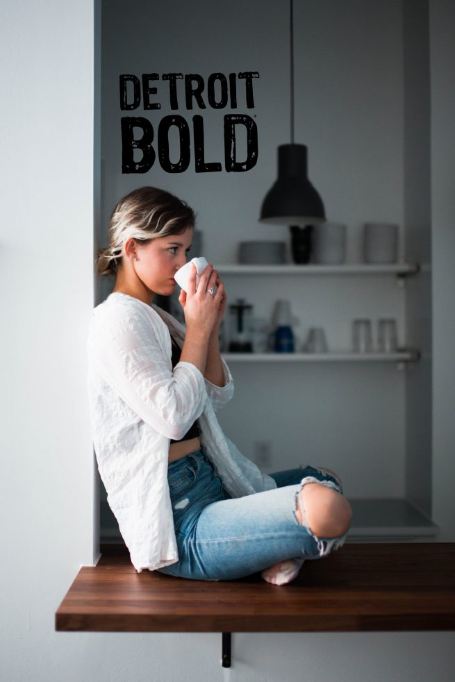 girl drinking the best coffee in the world detroit bold coffee strong coffee in background